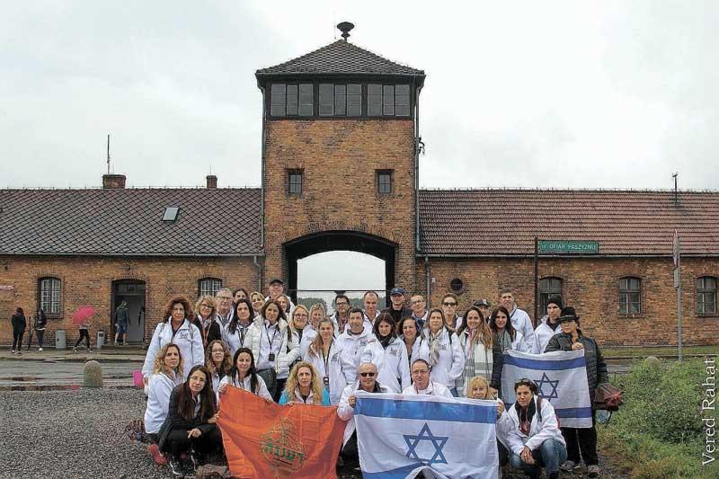 משלחת ההורים על רקע הכניסה למחנה אושוויץ-בירקנאו. צילום ורד רהט
