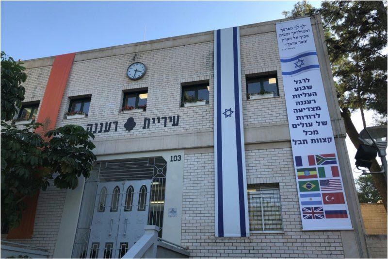 דגל ההצדעה לגלי העלייה שנתלה על בניין העירייה לצד דגל ישראל