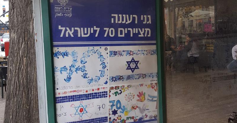 תחנת אוטובוס בעיר ובה פוסטר המורכב מכרזות דגלי ישראל בציור ילדי הגנים