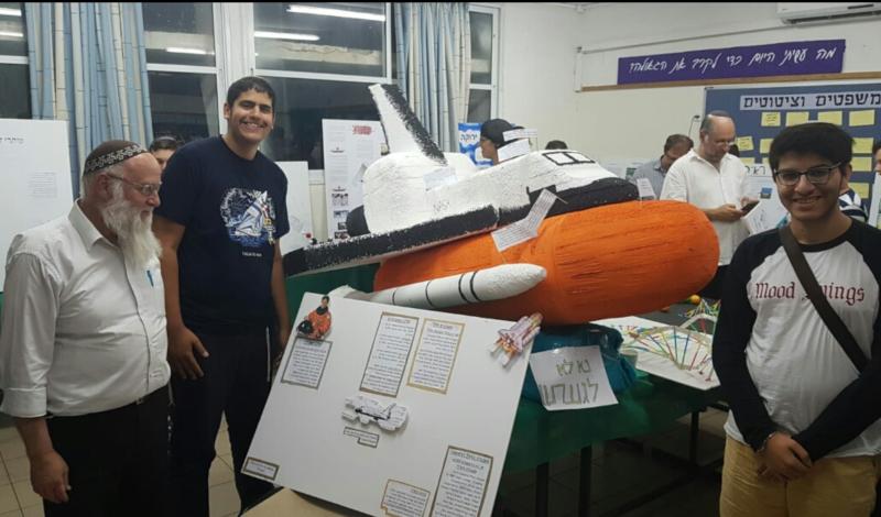התלמידים יאיר שמילא ועילאי גילה עם דגם מעבורת החלל שבנו, לצד המורה הרב אברהם שוורץ. צילום: שגיא רוזנבאום