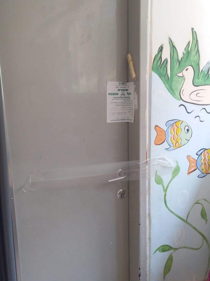 """דלת בגן תמר עם שלט """"אזהרה רעל"""" לאחר הדברה."""