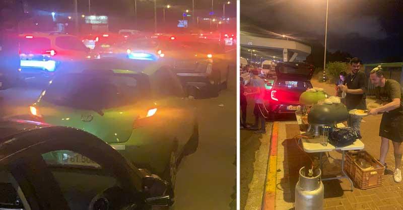 פקק ענק בכביש 2 בעקבות המחאה. דין אוחיון (מימין) וחברו מכינים פיצות לנהגי בפקק. צילומים: תום סימונוב