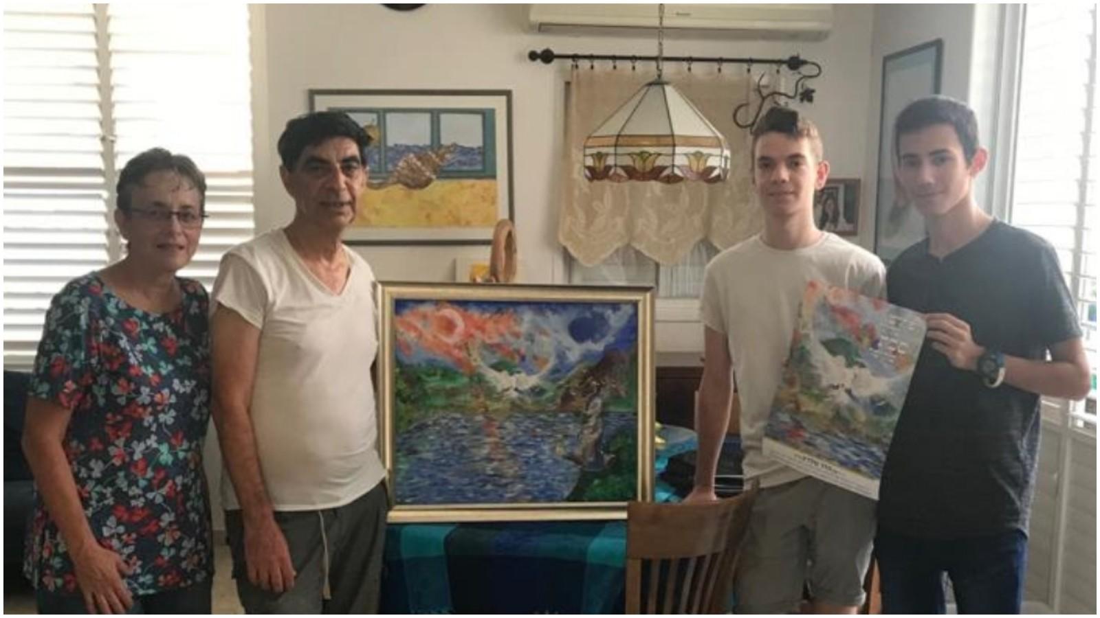 שי רוט וניר גלזר עם הוריו של הדר גולדין, שמחה ולאה, עם הכרזה לסוכה שעליה ציורו של הדר