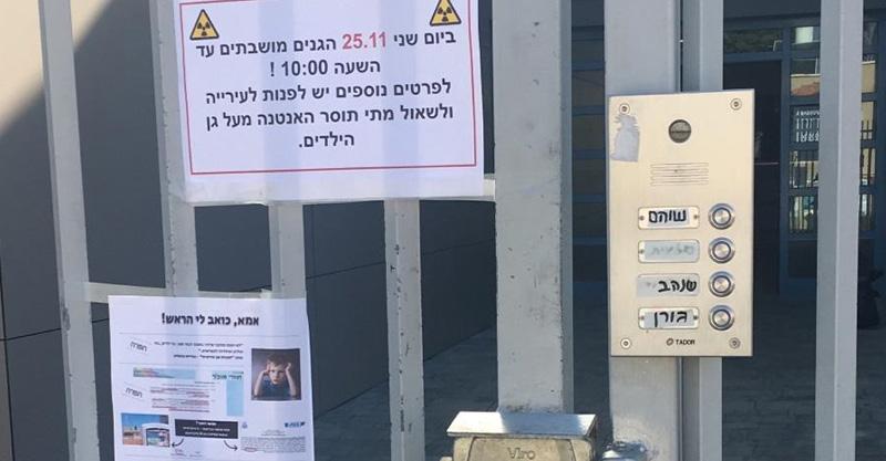 שלטים שנתלו על שער אשכול הגנים ברחוב נתן אלבז בגליל ים. צילום: מטה המאבק באנטנות הסלולריות